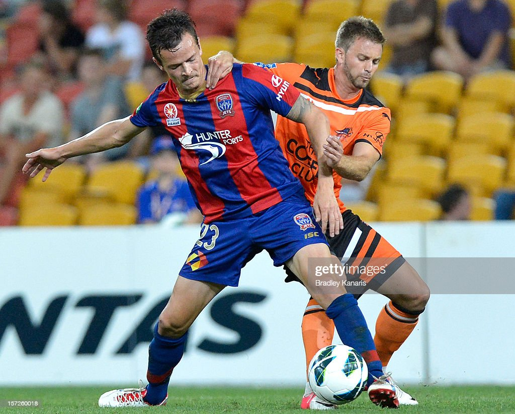 Ryan Griffiths of the Jets is chellenged by the defence of James Meyer of the Roar during the round nine ALeague match between the Brisbane Roar and...