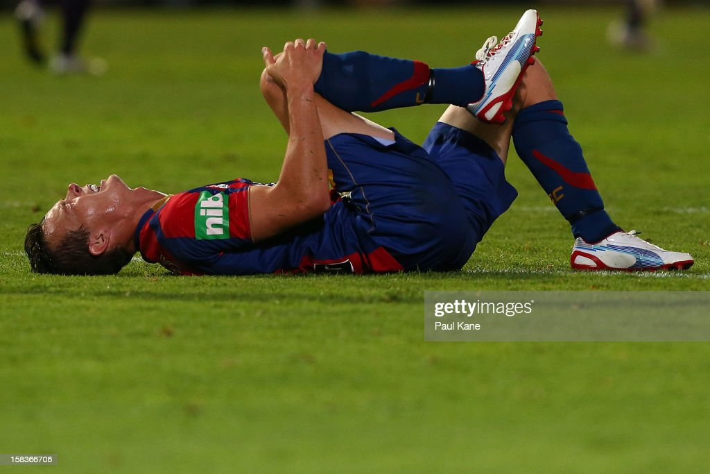 Ryan Griffiths of the Jets lies on thr ground after being tackled during the round 11 ALeague match between the Perth Glory and the Newcastle Jets at...