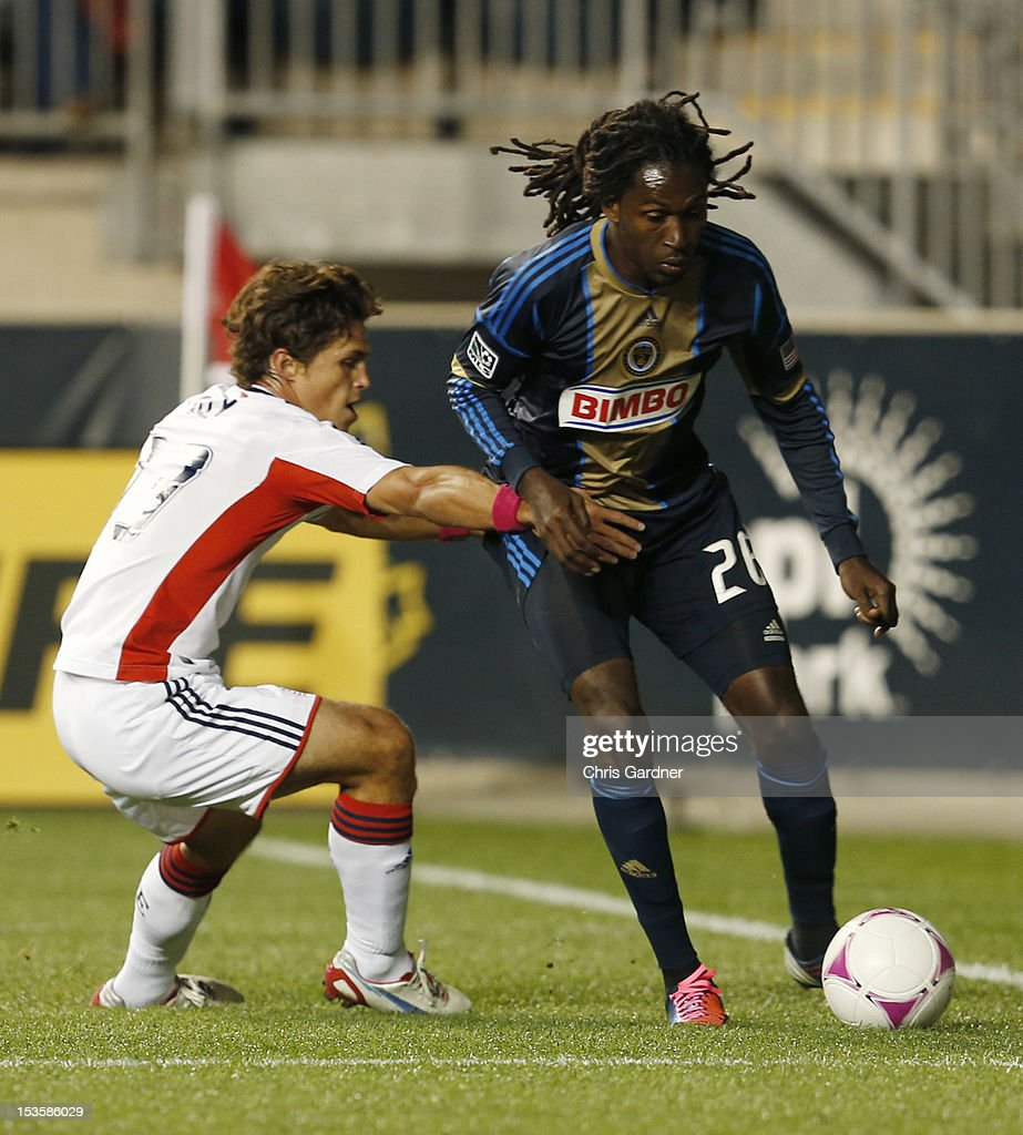Ryan Guy #13 of the New England Revolution tries to hold back Keon Daniel #26 of the Philadelphia Union as he pushes toward the goal at PPL Park on October 6, 2012 in Chester, Pennsylvania.