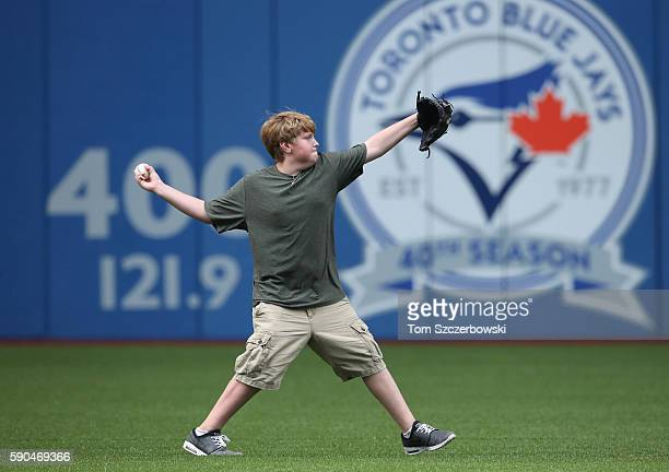 Ryan Halladay the son of former player Roy Halladay of the Toronto Blue Jays plays catch in the outfield after the game before which his father was...