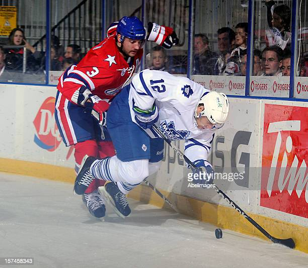 Ryan Hamilton of the Toronto Marlies is run down by T J Brennan of the Rochester Americans during AHL game action December 1 2012 at Ricoh Coliseum...