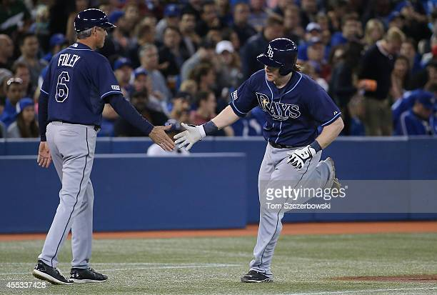 Ryan Hanigan of the Tampa Bay Rays is congratulated by third base caoch Tom Foley after hitting a solo home run in the third inning during MLB game...