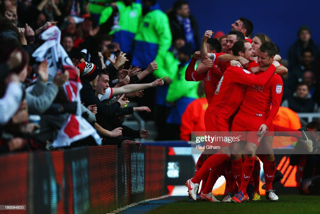 Ryan Harley (front left) of Milton Keynes Dons is swamped by team mates after scoring his sides third goal during the FA Cup with Budweiser Fourth Round match between Queens Park Rangers and Milton Keynes Dons at Loftus Road on January 26, 2013 in London, England.