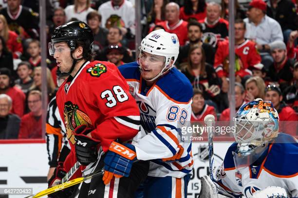 Ryan Hartman of the Chicago Blackhawks and Brandon Davidson of the Edmonton Oilers wait in position in front of goalie Cam Talbot in the first period...