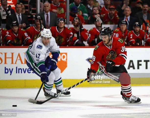Ryan Hartman of the Chicago Blackhawks and Drew Shore of the Vancouver Canucks move to the puck at the United Center on March 21 2017 in Chicago...