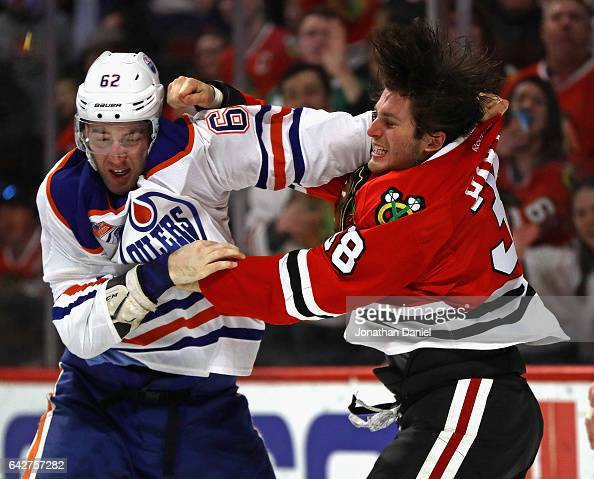 Ryan Hartman of the Chicago Blackhawks and Eric Gryba of the Edmonton Oilers fight in the second period at the United Center on February 18 2017 in...