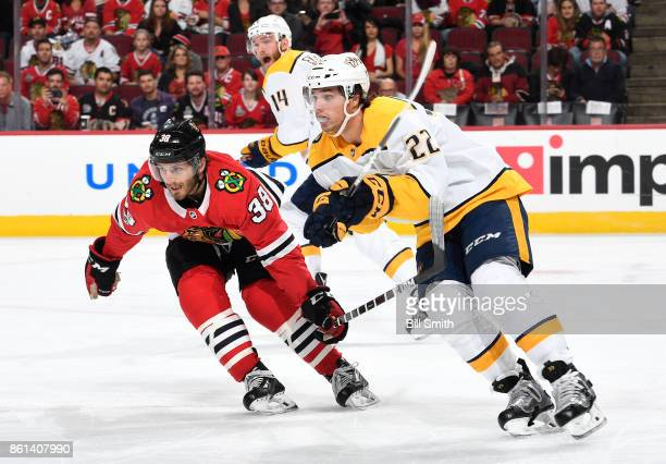 Ryan Hartman of the Chicago Blackhawks and Kevin Fiala of the Nashville Predators skate as Mattias Ekholm yells in the background in the first period...
