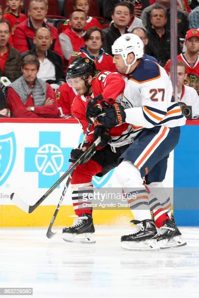 Ryan Hartman of the Chicago Blackhawks and Milan Lucic of the Edmonton Oilers get physical in the first period at the United Center on October 19...