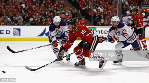Ryan Hartman of the Chicago Blackhawks chases the puck under pressure from Adam Larsson and Iiro Pakarinen of the Edmonton Oilers at the United...