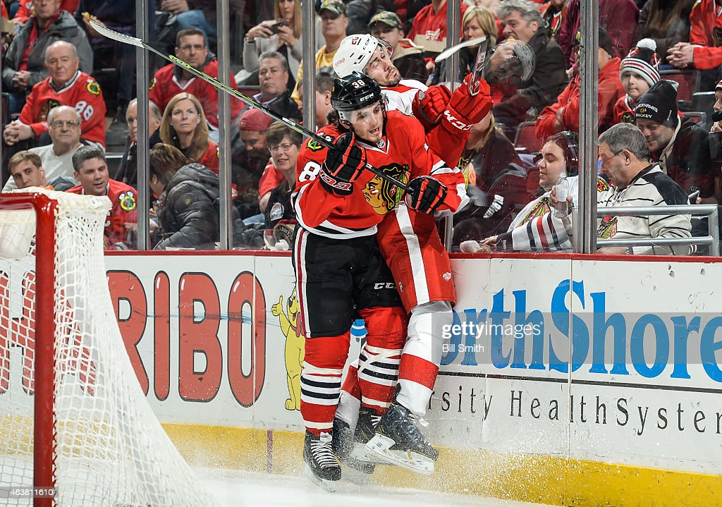 <a gi-track='captionPersonalityLinkClicked' href=/galleries/search?phrase=Ryan+Hartman&family=editorial&specificpeople=9156569 ng-click='$event.stopPropagation()'>Ryan Hartman</a> #38 of the Chicago Blackhawks checks Drew Miller #20 of the Detroit Red Wings into the glass during the NHL game at the United Center on February 18, 2015 in Chicago, Illinois.