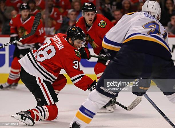 Ryan Hartman of the Chicago Blackhawks scores his first NHL goal past Robert Bortuzzo of the St Louis Blues during the season opening game at the...