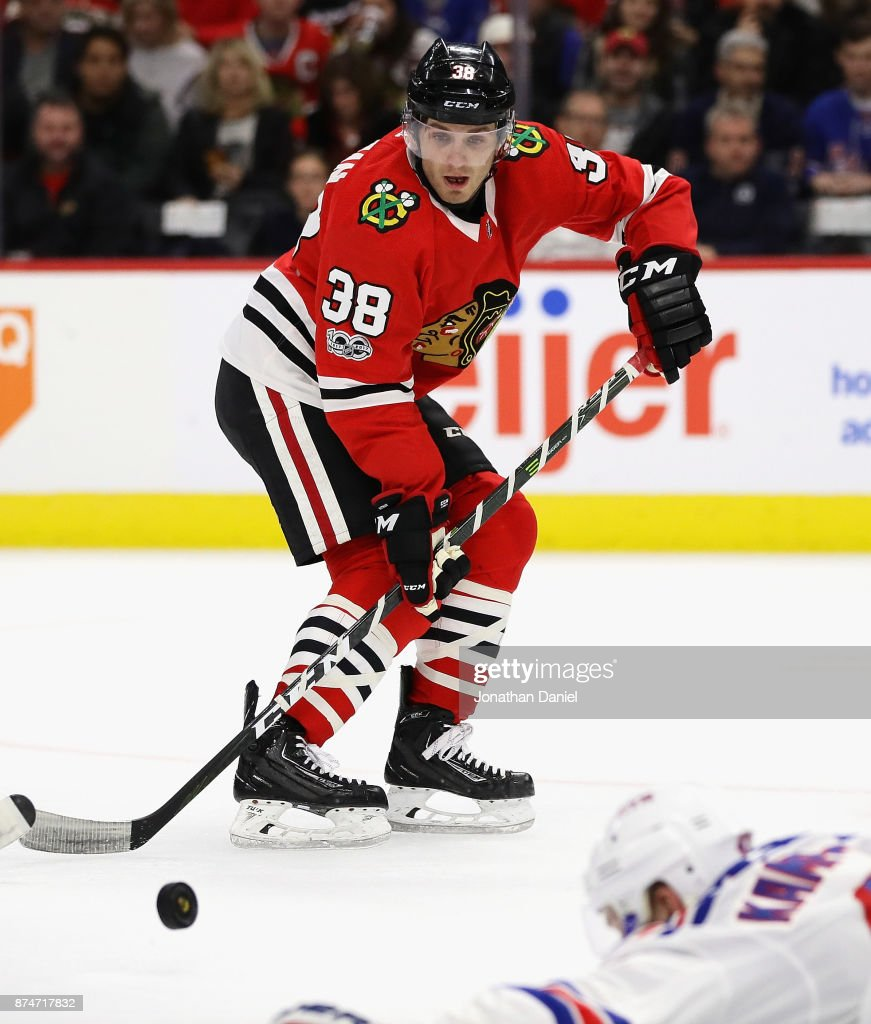 Ryan Hartman #38 of the Chicago Blackhawks takes a pass over Steven Kampfer #47 of the New York Rangers at the United Center on November 15, 2017 in Chicago, Illinois.