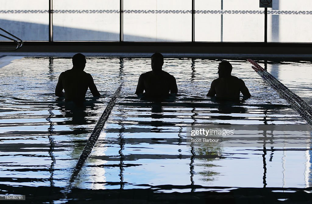 Ryan Hinchcliffe, Lagi Setu and Slade Griffin of the Storm walk in the water during a Melbourne Storm NRL recovery session at AAMI Park on March 11, 2013 in Melbourne, Australia.
