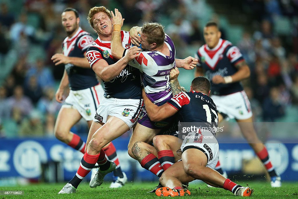 Ryan Hinchcliffe of the Storm is tackled by Dylan Napa and Sio Siua Taukeiaho of the Roosters during the NRL qualifying final match between the Sydney Roosters and the Melbourne Storm at Allianz Stadium on September 11, 2015 in Sydney, Australia.