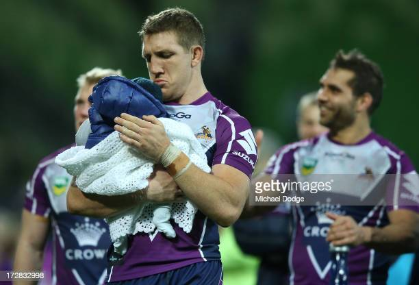 Ryan Hoffman of the Storm celebrates the win with his baby son Zach Hoffman during the round 17 NRL match between the Melbourne Storm and the...