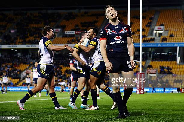 Ryan Hoffman of the Warriors reacts as Justin O'Neill of the Cowboys celebrates a try with his teammates during the round 24 NRL match between the...
