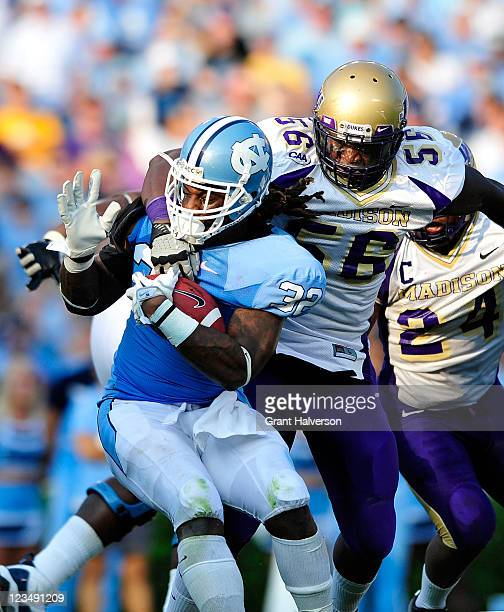 Ryan Houston of the North Carolina Tar Heels spins out of a tackle by Jordan stanton of the James Madison Dukes during the fourth quarter at Kenan...