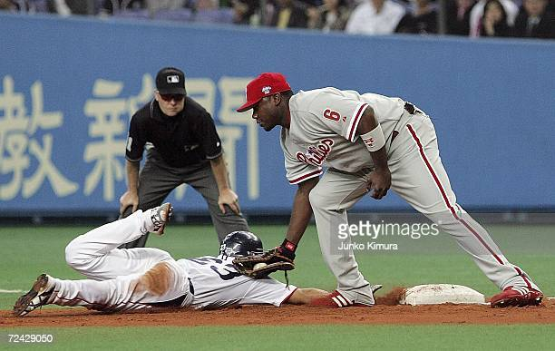 Ryan Howard of of the Philadelphia Phillies fails to tag out Norichika Aoki of Tokyo Yakult Swallows at the first base during the Aeon All Star...
