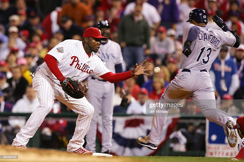 Ryan Howard #6 of the Philadelphia Phillies barehands the ball but cannot catch Carl Crawford #13 of the Tampa Bay Rays during game three of the 2008 MLB World Series on October 25, 2008 at Citizens Bank Park in Philadelphia, Pennsylvania.