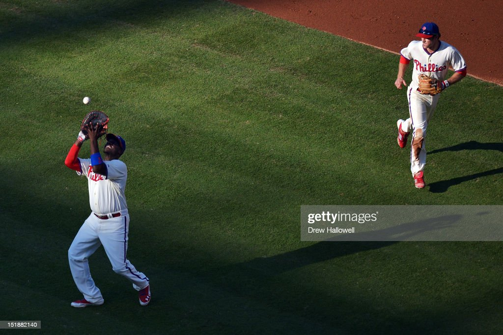 <a gi-track='captionPersonalityLinkClicked' href=/galleries/search?phrase=Ryan+Howard&family=editorial&specificpeople=551402 ng-click='$event.stopPropagation()'>Ryan Howard</a> #6 of the Philadelphia Phillies catches a fly ball as teammate <a gi-track='captionPersonalityLinkClicked' href=/galleries/search?phrase=Chase+Utley&family=editorial&specificpeople=161391 ng-click='$event.stopPropagation()'>Chase Utley</a> #26 runs in to back him up during the game against the Miami Marlins at Citizens Bank Park on September 12, 2012 in Philadelphia, Pennsylvania.