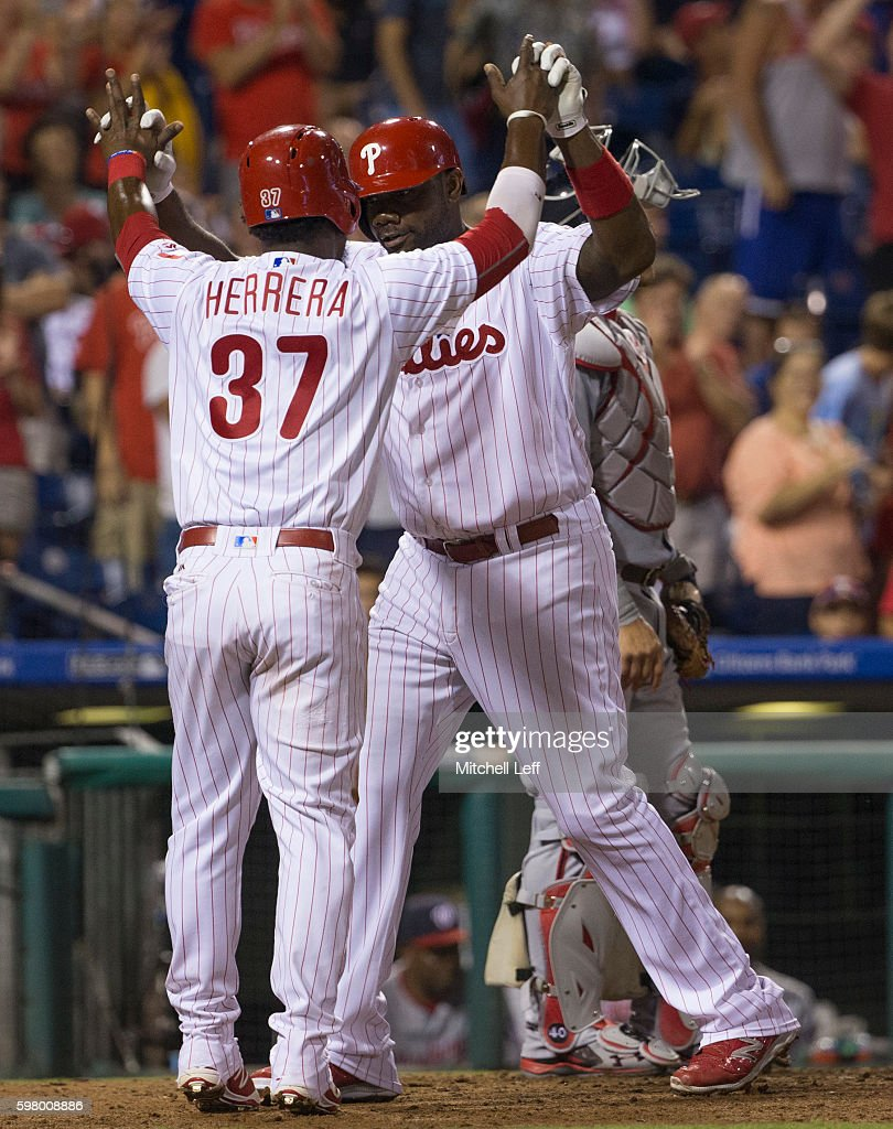 Ryan Howard of the Philadelphia Phillies high fives Odubel Herrera after hitting a two run home run in the bottom of the seventh inning against the...