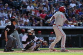 Ryan Howard of the Philadelphia Phillies takes an at bat as catcher Jordan Pacheco of the Colorado Rockies backs up the plate and umpire Chris Segal...