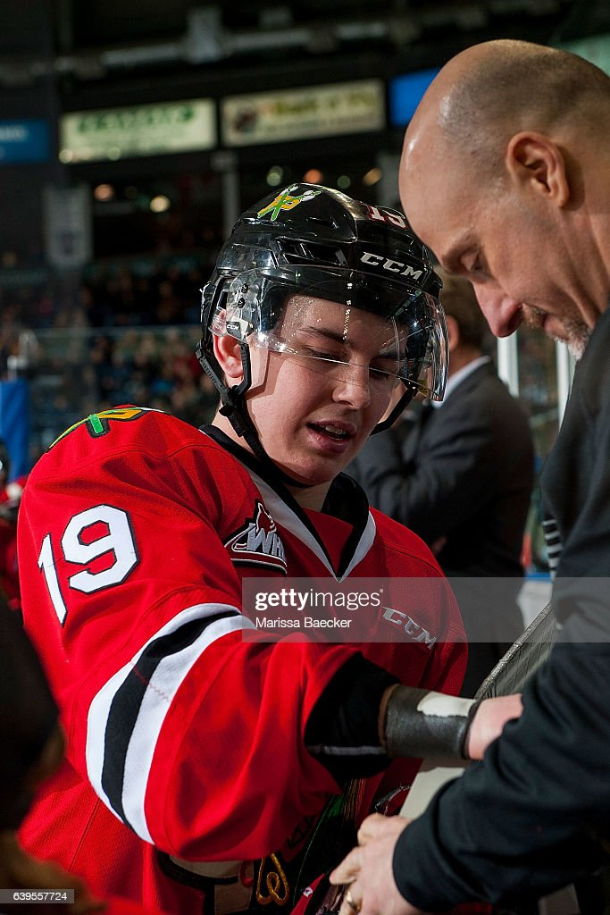 Ryan Hughes #19 of the Portland Winterhawks stands on the bench and gets a wrist taping from athletic therapist Rich Campbell on January 21, 2017 at Prospera Place in Kelowna, British Columbia, Canada.