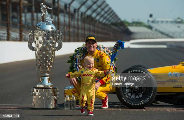 Ryan HunterReay driver of the Andretti Autosport Dallara Honda and his son Ryden pose with the Borg Warner Trophy at the yard of bricks during the...