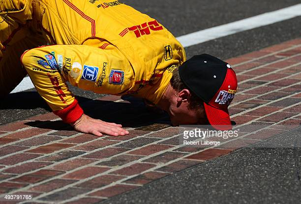 Ryan HunterReay driver of the Andretti Autosport Dallara Honda celebrates by kissing the bricks at the start finish line after winning the 98th...