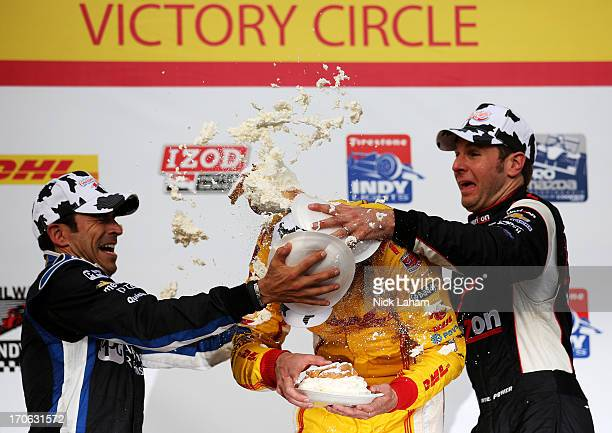 Ryan HunterReay driver of the Andretti Autosport DHL Chevrolet is hit with cream puffs by second place Helio Castroneves of Brazil driver of the PPG...