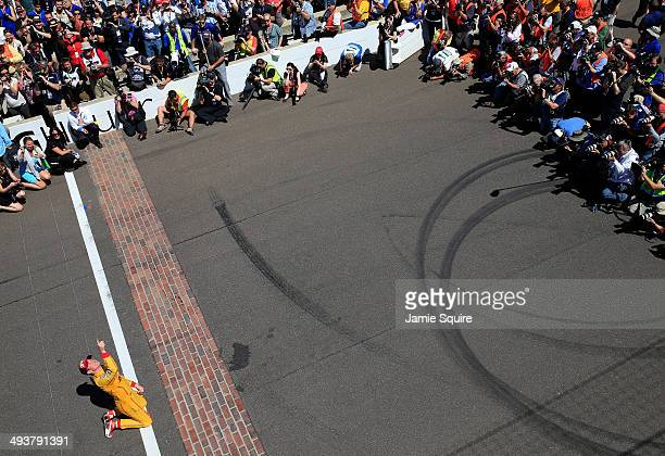 Ryan HunterReay driver of the Andretti Autosport DHL Honda looks skyward as he kisses the bricks at the finish line after winning the 98th running of...