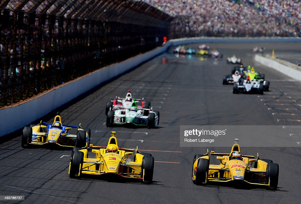 <a gi-track='captionPersonalityLinkClicked' href=/galleries/search?phrase=Ryan+Hunter-Reay&family=editorial&specificpeople=2197753 ng-click='$event.stopPropagation()'>Ryan Hunter-Reay</a>, driver of the #28 DHL Andretti Autosport Honda Dallara, Helio Castroneves of Brazil, driver of the #3 Pennzoil Ultra Platinum Penske Chevrolet Dallara, and <a gi-track='captionPersonalityLinkClicked' href=/galleries/search?phrase=Marco+Andretti&family=editorial&specificpeople=540446 ng-click='$event.stopPropagation()'>Marco Andretti</a>, driver of the #25 Snapple Andretti Autosport Honda Dallara, race during the 98th running of the Indianapolis 500 at Indianapolis Motorspeedway on May 25, 2014 in Indianapolis, Indiana.