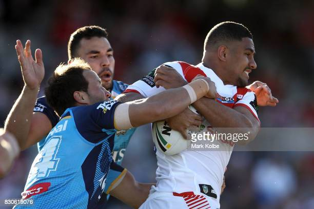Ryan James and Tyrone Roberts of the Titans tackle Nene MacDonald of the Dragons during the round 23 NRL match between the St George Illawarra...