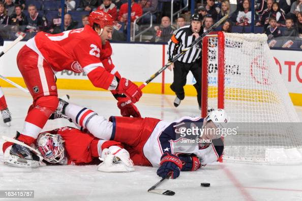 Ryan Johansen of the Columbus Blue Jackets continues to play the puck after being checked by Kyle Quincey of the Detroit Red Wings during the first...