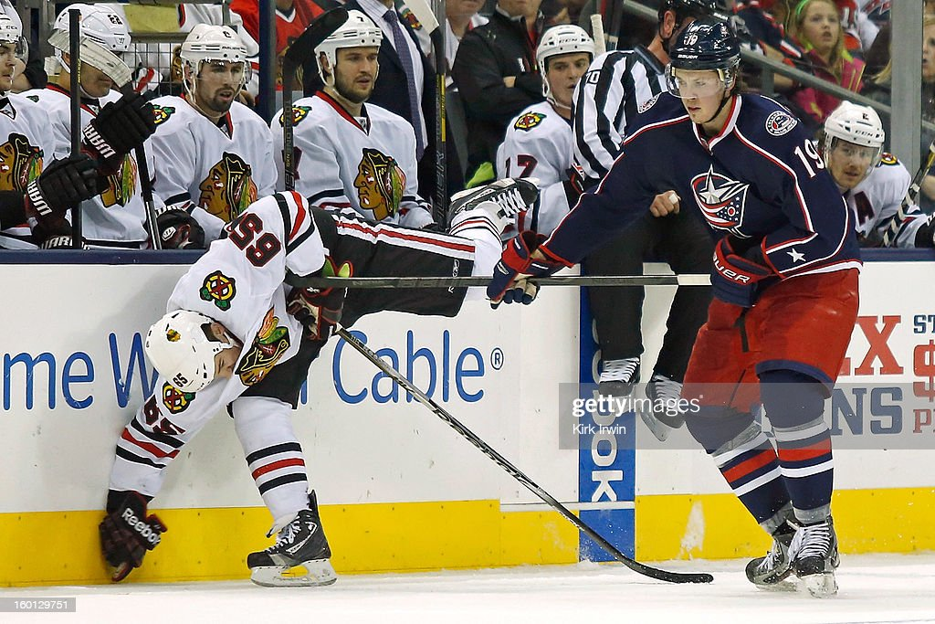 Ryan Johansen #19 of the Columbus Blue Jackets hooks Andrew Shaw #65 of the Chicago Blackhawks during the third period on January 26, 2013 at Nationwide Arena in Columbus, Ohio. Chicago defeated Columbus 3-2.