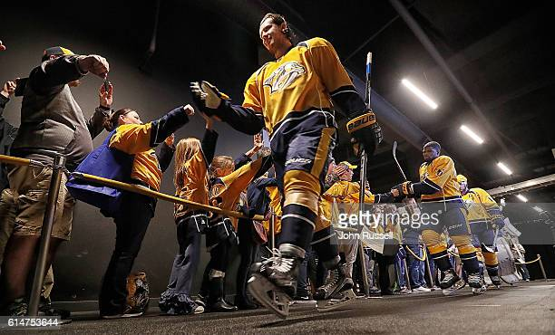 Ryan Johansen of the Nashville Predators taps hands with fans as the team walks to the ice for warmups prior to an NHL game against Chicago...