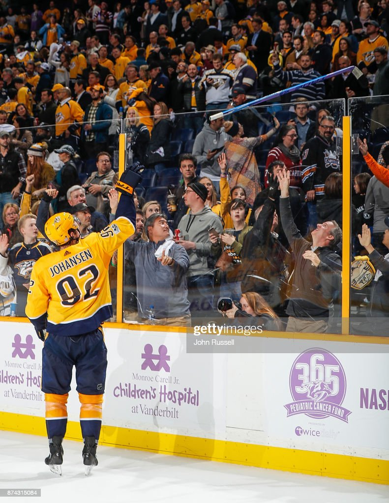 Ryan Johansen #92 of the Nashville Predators tosses his Hockey Fights Cancer stick to a fan after a 6-3 win against the Washington Capitals during an NHL game at Bridgestone Arena on November 14, 2017 in Nashville, Tennessee.