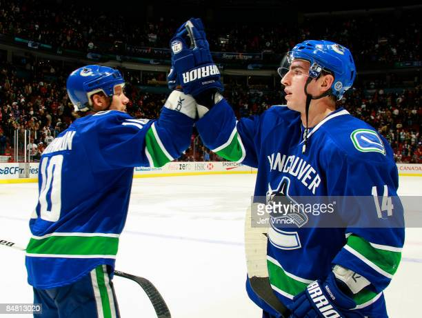 Ryan Johnson and Alex Burrows of the Vancouver Canucks celebrate their win over the Montreal Canadiens during their game at General Motors Place on...