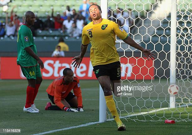 Ryan Johnson of Jamaica celebrates a goal as Leon Johnson and goalkeeper Andray Baptiste of Grenada look on during the first half of the CONCACAF...
