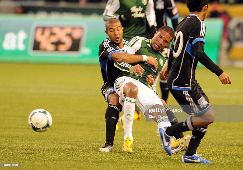 Ryan Johnson #9 of Portland Timbers is dragfged down by Justin Morrow #15 of San Jose Earthquakes during the first half of the game at Jeld-Wen Field on February 17, 2013 in Portland, Oregon.