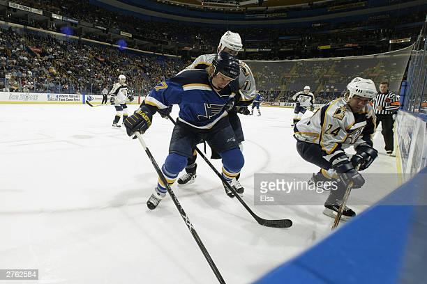 Ryan Johnson of the St Louis Blues digs for the puck with David Legwand and Scott Walker of the Nashville Predators on October 28 2003 at the Savvis...