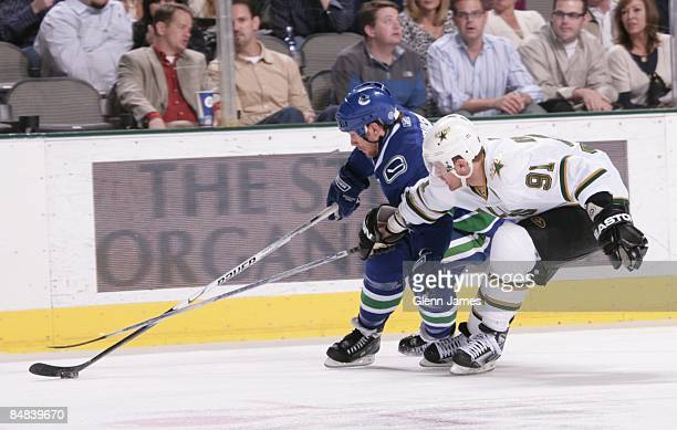 Ryan Johnson of the Vancouver Canucks tries to keep the puck away against Brad Richards of the Dallas Stars on February 13 2009 at the American...