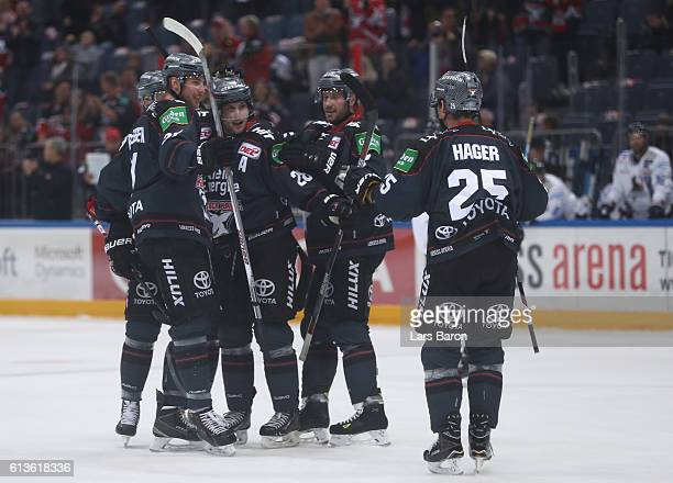 Ryan Jones of Koeln celebrates with team mates after scoring his teams third goal during the DEL match between Koelner Haie and Iserlohn Roosters at...