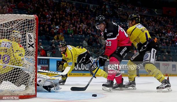 Ryan Jones of Koelner Haie and Nicolas StPierre of Krefeld Pinguine battle for the puck during the DEL Ice Hockey match between Koelner Haie and...