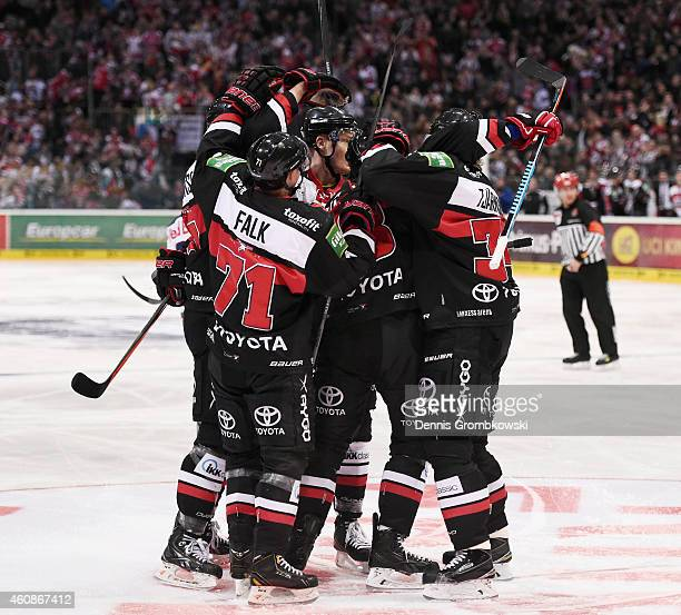Ryan Jones of Koelner Haie celebrates with team mates as he scores the opening goal during the DEL Ice Hockey game between Koelner Haie and EHC Red...