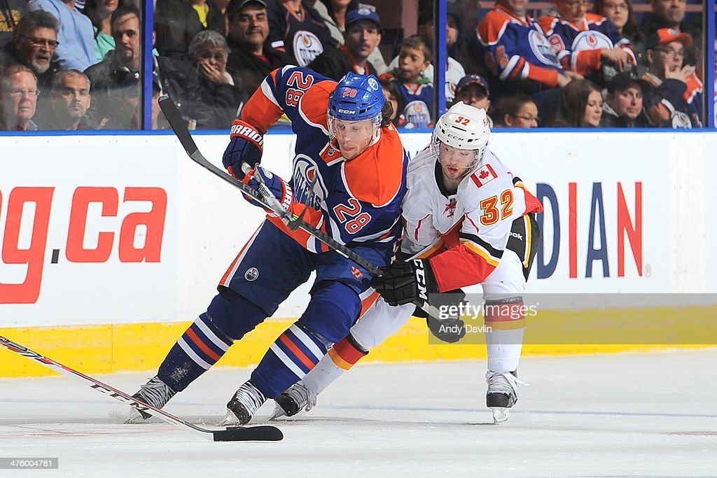 Ryan Jones #28 of the Edmonton Oilers battles for the puck against <a gi-track='captionPersonalityLinkClicked' href=/galleries/search?phrase=Paul+Byron+-+Ice+Hockey+Player&family=editorial&specificpeople=4535697 ng-click='$event.stopPropagation()'>Paul Byron</a> #32 of the Calgary Flames on March 1, 2014 at Rexall Place in Edmonton, Alberta, Canada.