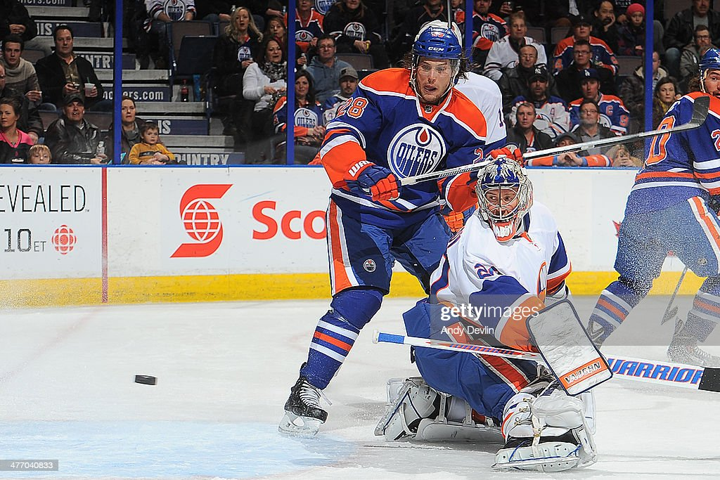 Ryan Jones #28 of the Edmonton Oilers crashes the net as goalie Evgeni Nabokov #20 of the New York Islanders watches the puck fly past on March 6, 2014 at Rexall Place in Edmonton, Alberta, Canada.