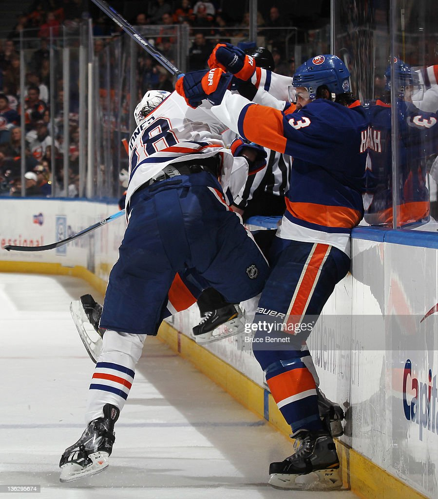 Ryan Jones #28 of the Edmonton Oilers hits <a gi-track='captionPersonalityLinkClicked' href=/galleries/search?phrase=Travis+Hamonic&family=editorial&specificpeople=4605791 ng-click='$event.stopPropagation()'>Travis Hamonic</a> #3 of the New York Islanders at the Nassau Veterans Memorial Coliseum on December 31, 2011 in Uniondale, New York. The Islanders defeated the Oilers 4-1.