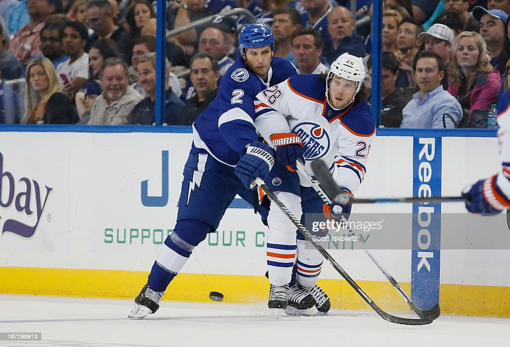 Ryan Jones #28 of the Edmonton Oilers passes the puck against <a gi-track='captionPersonalityLinkClicked' href=/galleries/search?phrase=Eric+Brewer&family=editorial&specificpeople=202144 ng-click='$event.stopPropagation()'>Eric Brewer</a> #2 of the Tampa Bay Lightning during the second period at Tampa Bay Times Forum on November 7, 2013 in Tampa, Florida.