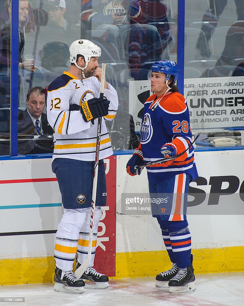 Ryan Jones #28 of the Edmonton Oilers talks with John Scott #32 of the Buffalo Sabres prior to an NHL game at Rexall Place on March 20, 2014 in Edmonton, Alberta, Canada.